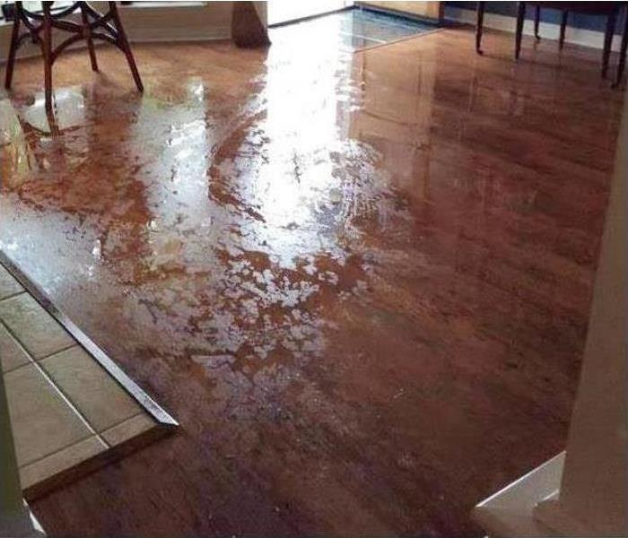A wet hardwood floor in a room of a house after water damage struck