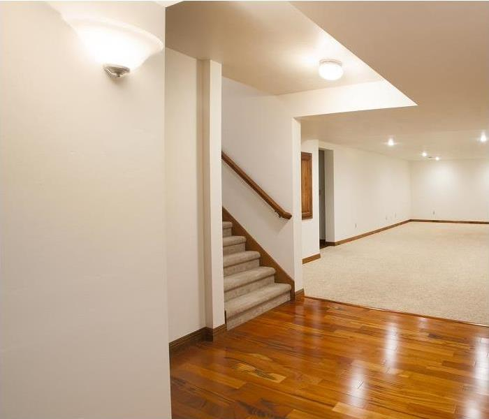 View of empty finished basement; carpeted and hardwood floors